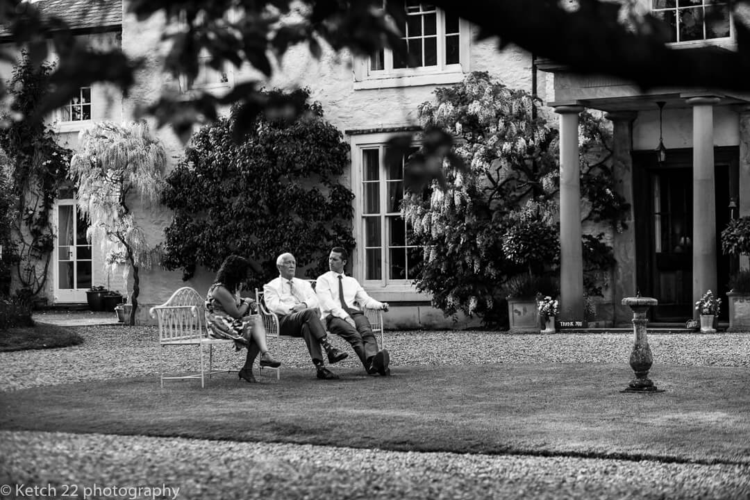 Wedding guests chat on bench in garden