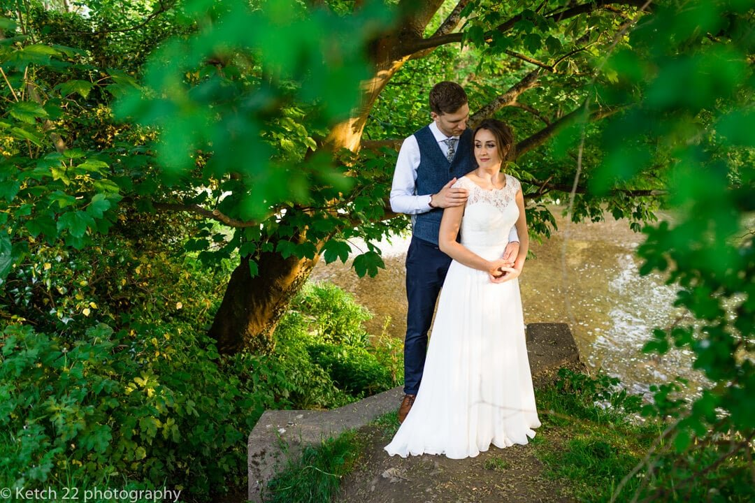 Portrait of bride and groom stood by a river and green trees
