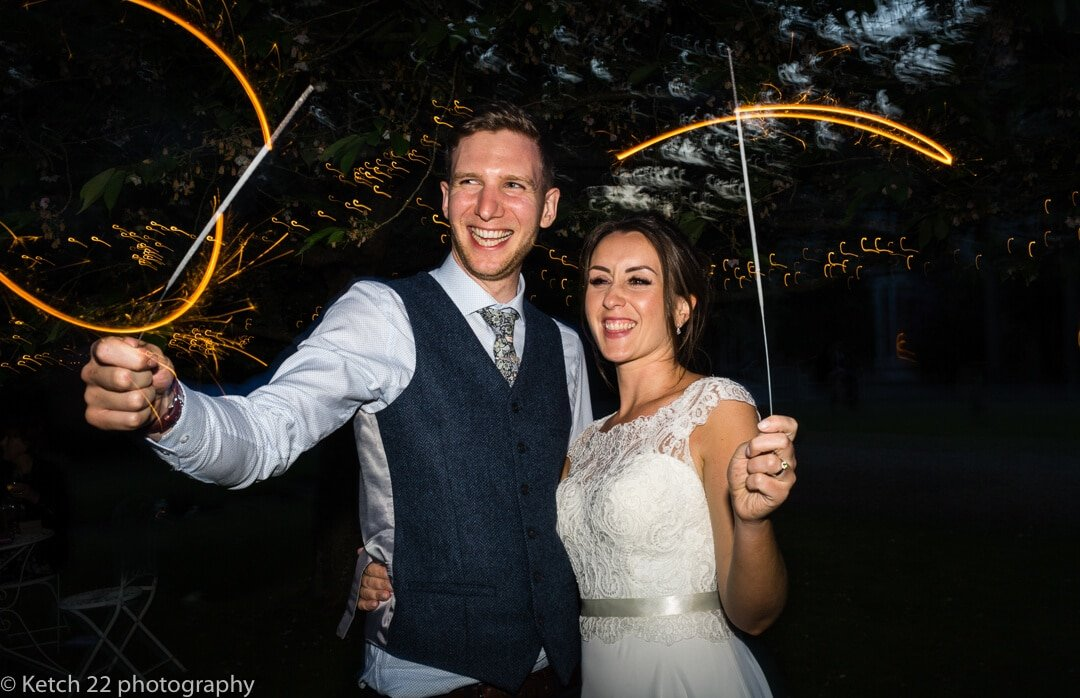 Portrait of bride and groom playing with sparklers