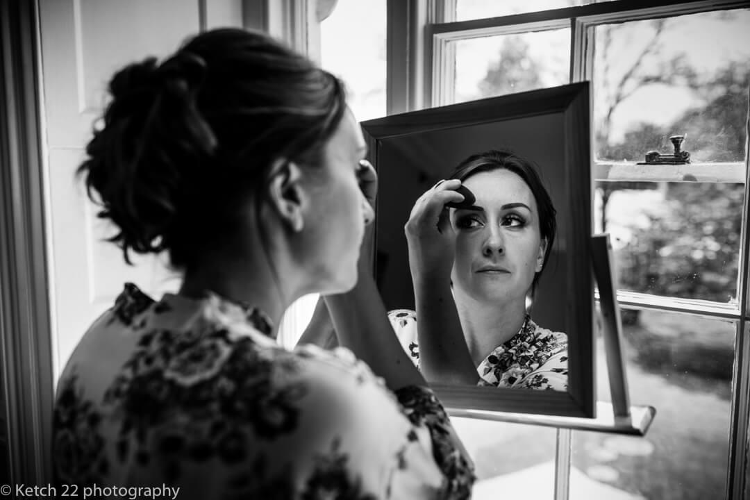 Bride looking in mirror and putting on makeup at wedding