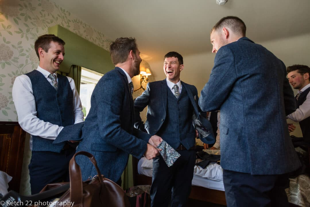 Groomsmen laughing at wedding preparations at The Lion Hotel in Herefordshire