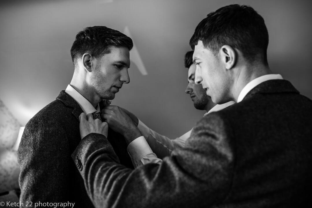 Best man helping groom at wedding preparations