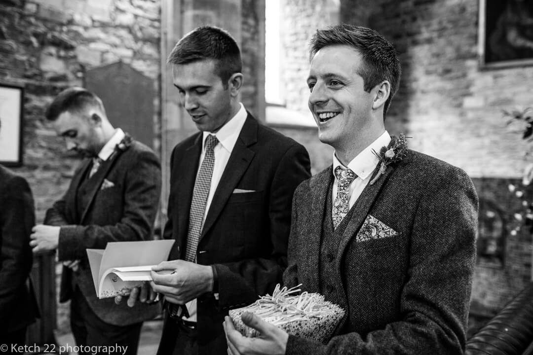 Groomsmen handing out order of service in church