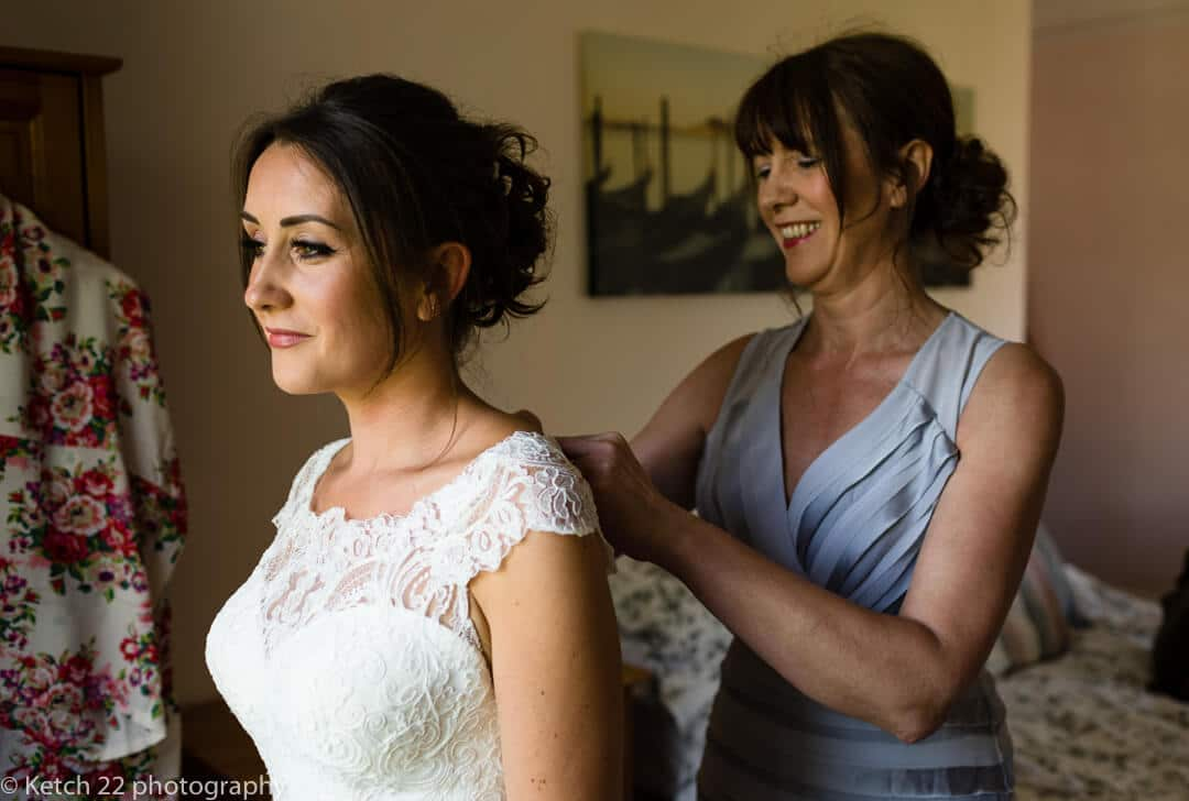 Mother helping bride get ready at wedding