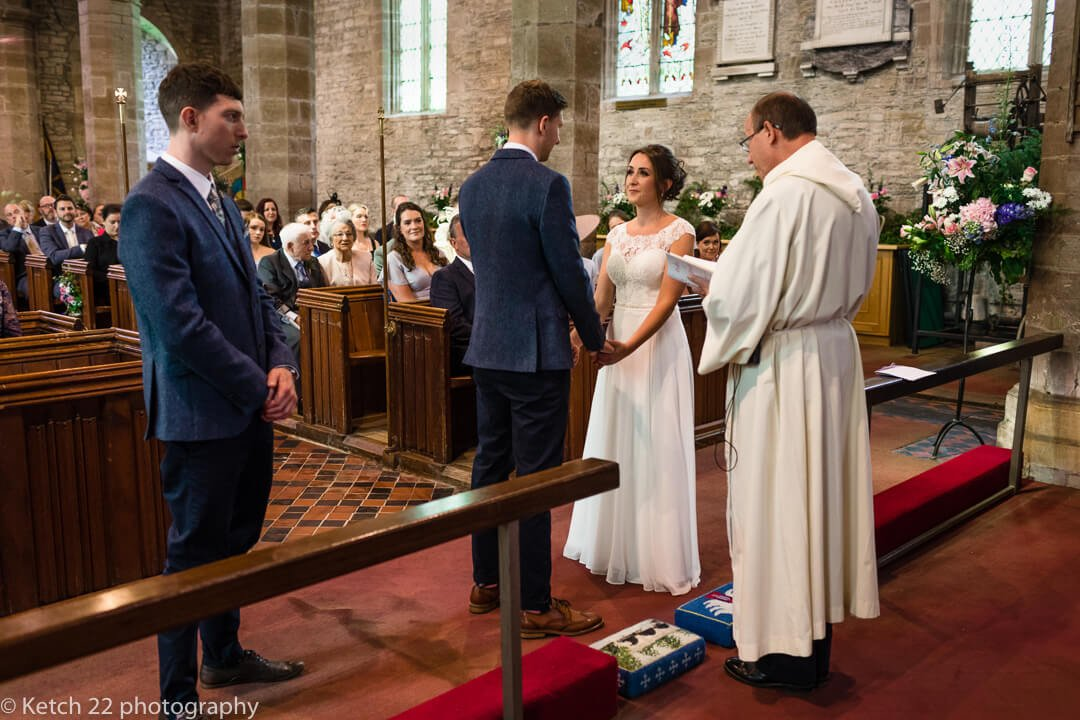 Vicar addressing bride and groom at Church wedding ceremony