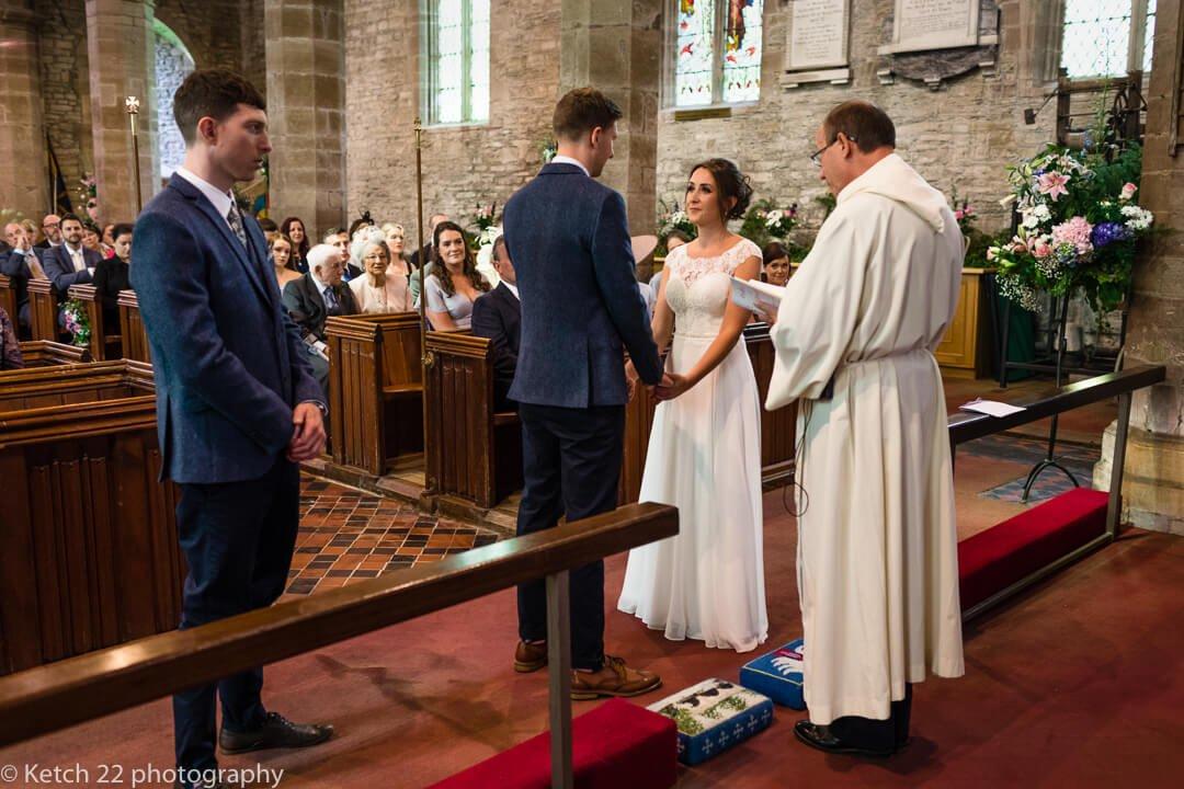 Vicar addressing bride and groom at Church wedding ceremony