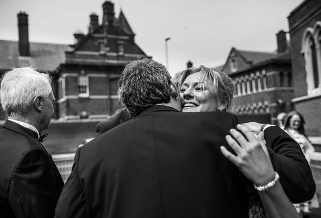 Bridesmaid hugging groom after wedding