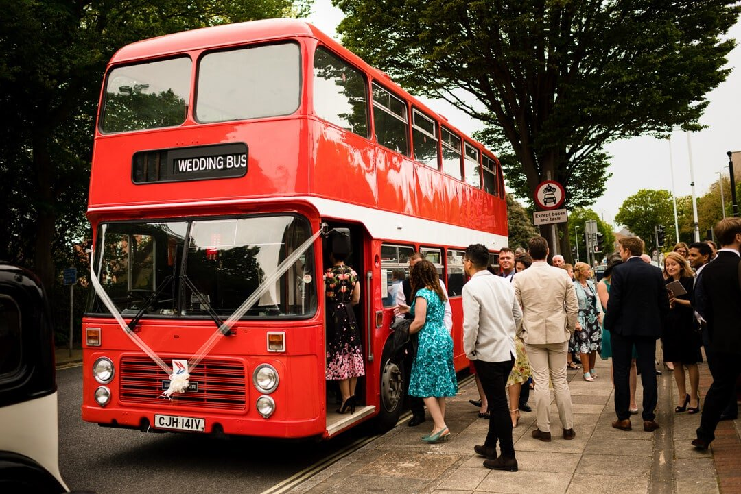 Wedding guests getting on red double decker bus