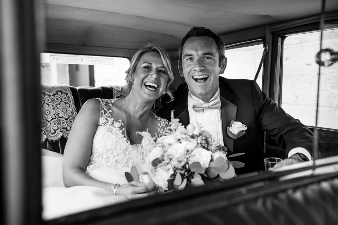 Bride and groom laughing in wedding car
