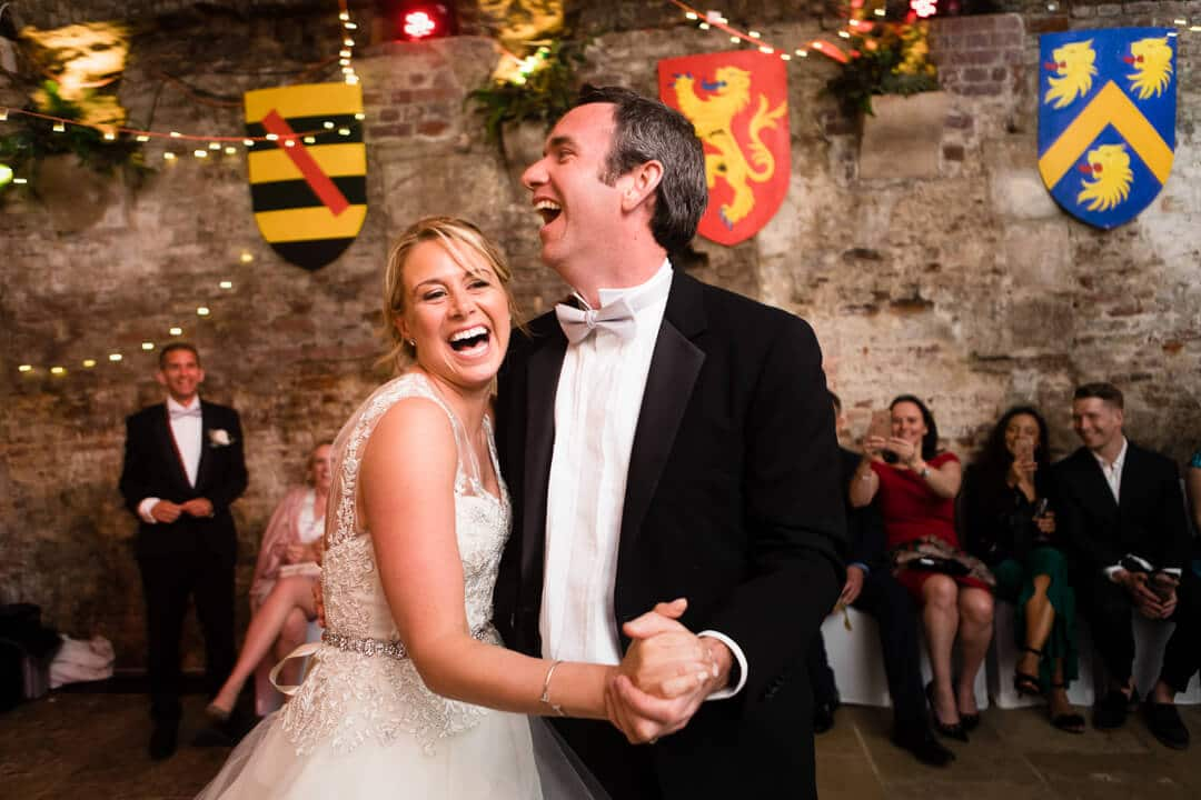 Reportage weding photo of bride and groom laughing at first dance