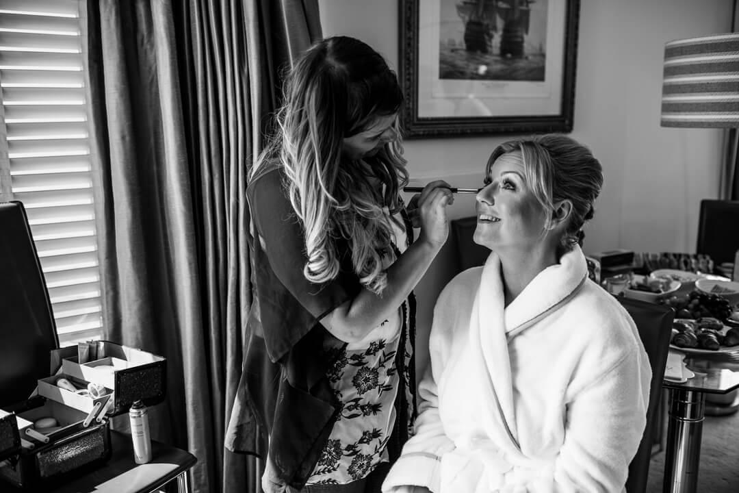 Bridesmaid having make up applied at wedding preparation