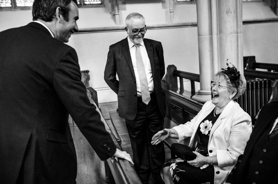Groom greeting grandma in church before wedding ceremony