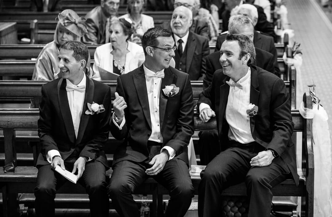 Groom enjoying joke with best man before wedding ceremony