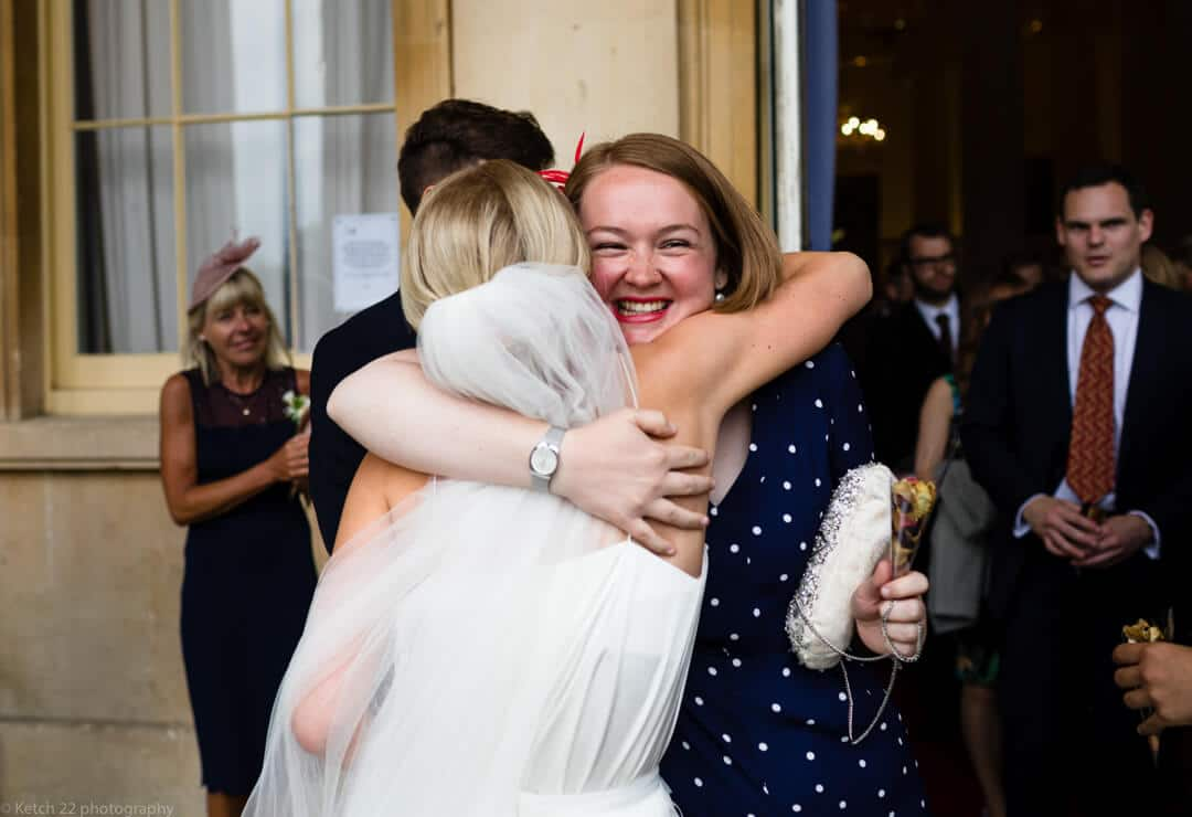 Wedding guest hugging bride at Piiville Pump rooms Cheltenham
