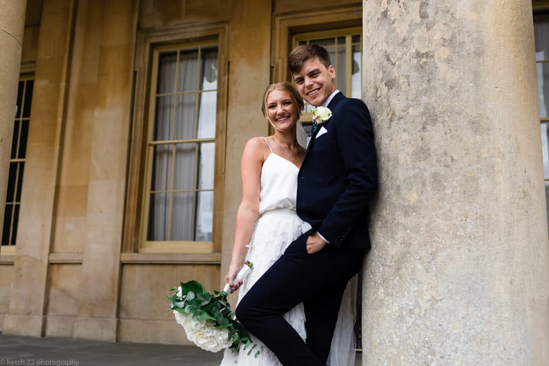 Bride and groom leaning on pillar at Cheltenham wedding