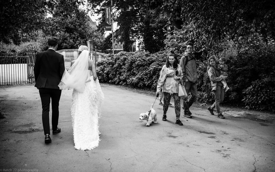 Bride and groom walking through park with members of public watching