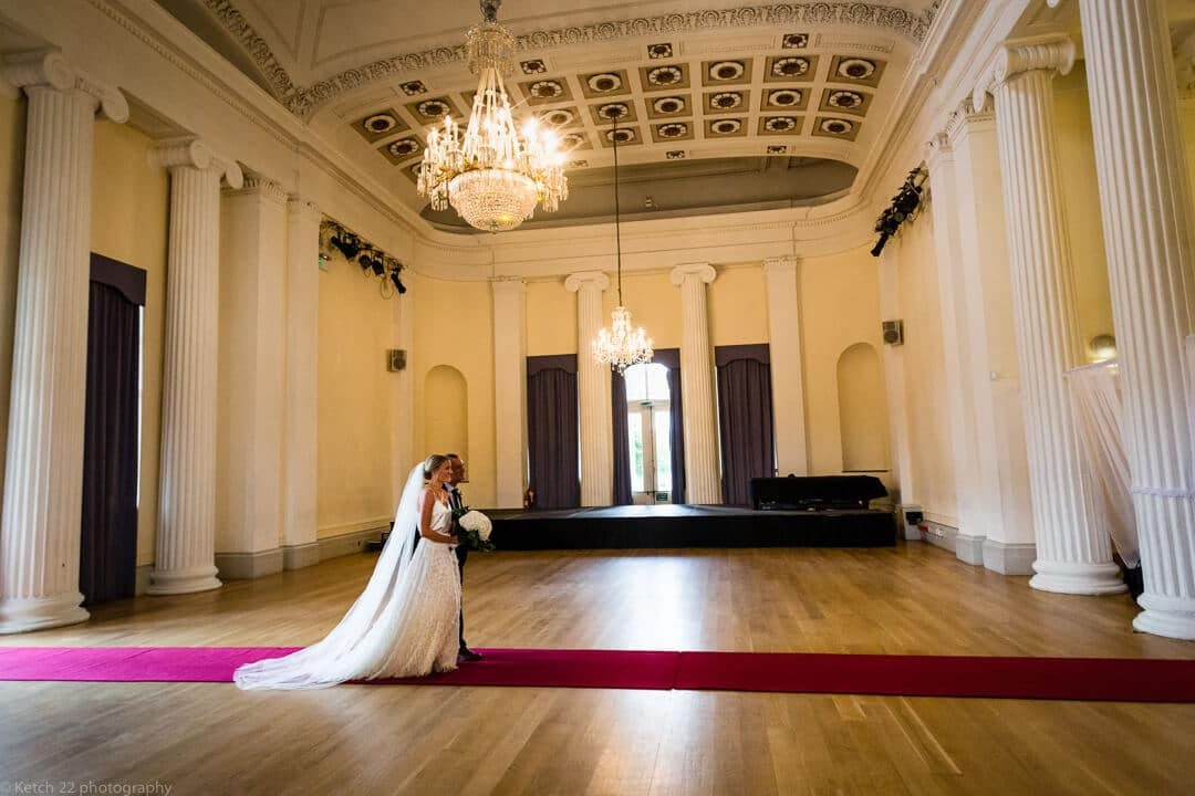 Bride walking inside Pittville Pump rooms wedding