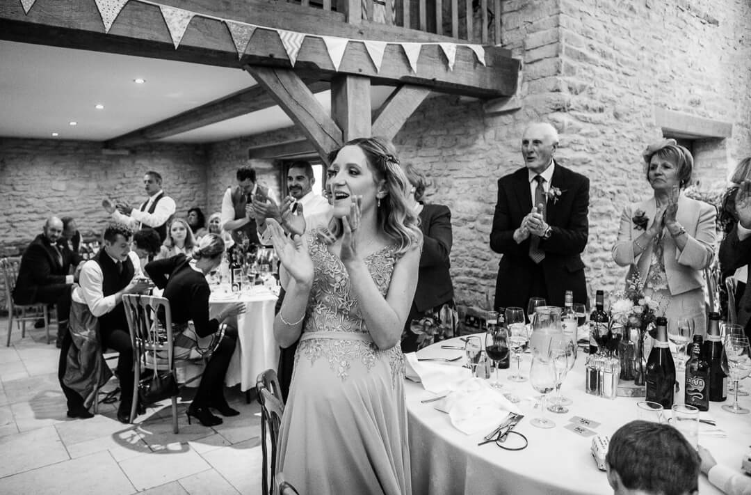 Bridesmaid cheering at wedding speeches