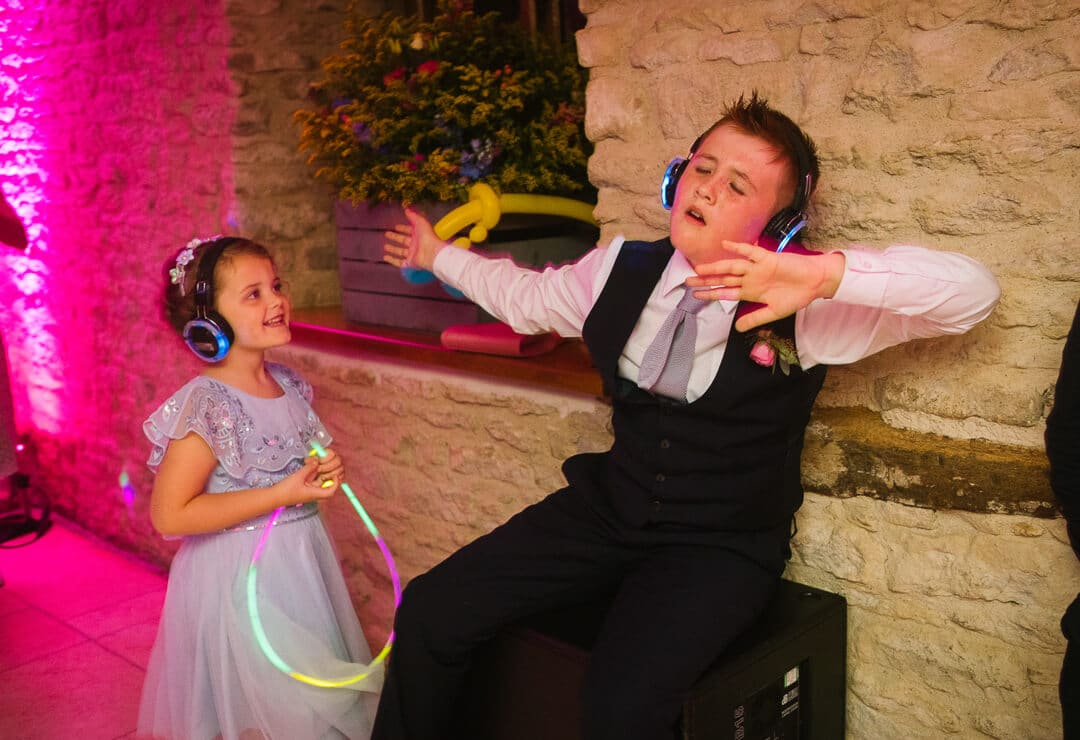 Page boy and flower girl dancing with head phones on
