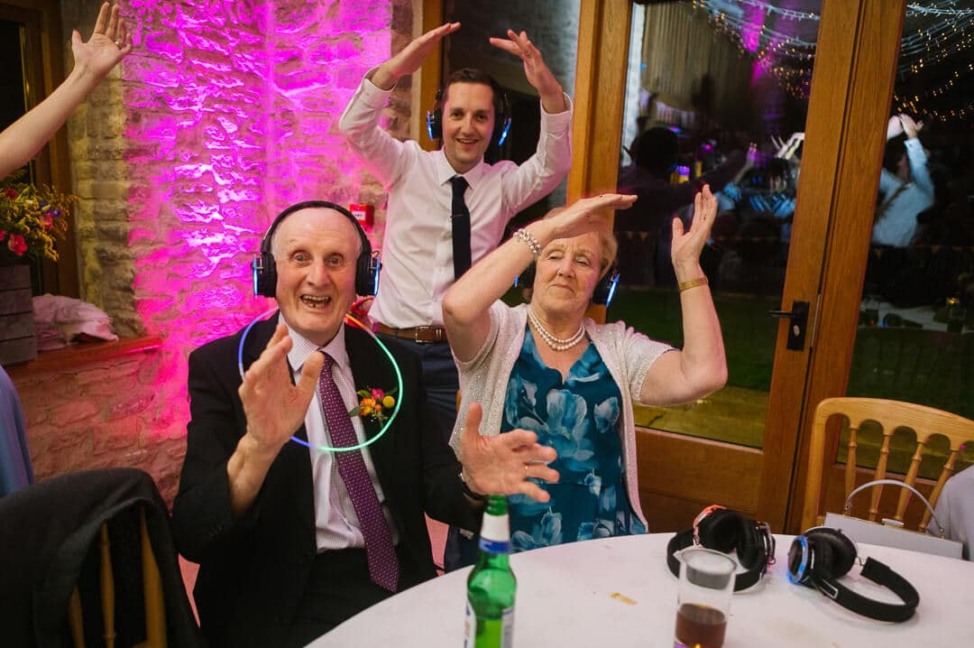 Grand dad and Grand mother enjoying silent clubbing at Kingscote Barn Wedding