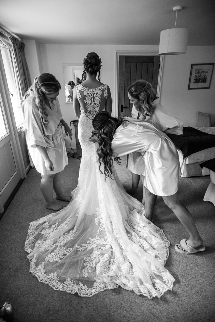 Full length view of bride putting on wedding dress