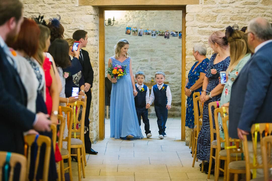 Bridesmaid and page boys enter wedding ceremony
