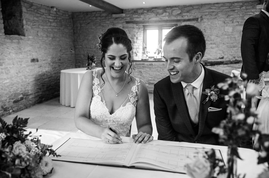 Brie and groom signing the registrar at Gloucestershire Wedding