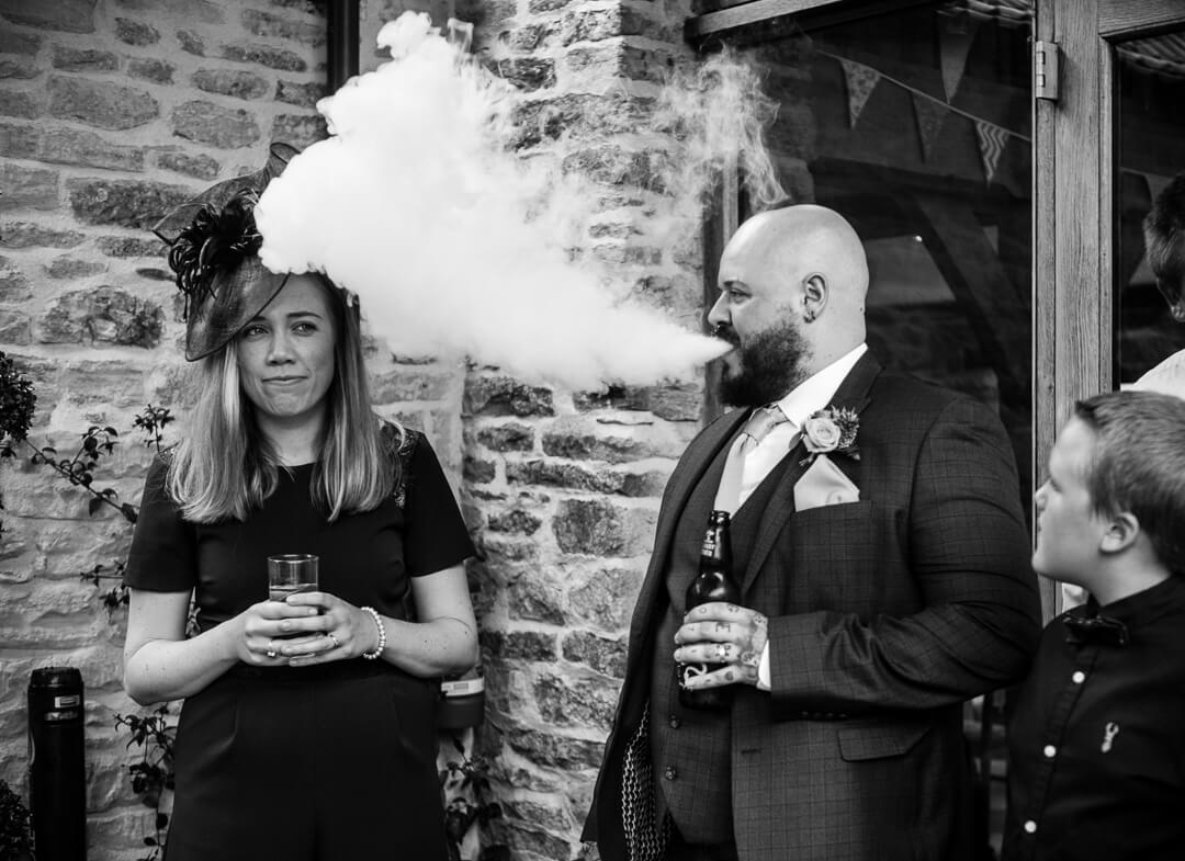Best man puffing on vape stick at Kingscote Barn Wedding