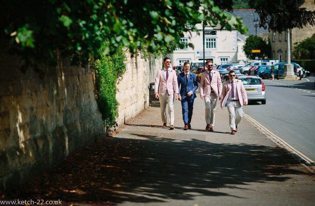 Groom and groomsmen walking down street at Winchcombe wedding in Gloucestershire