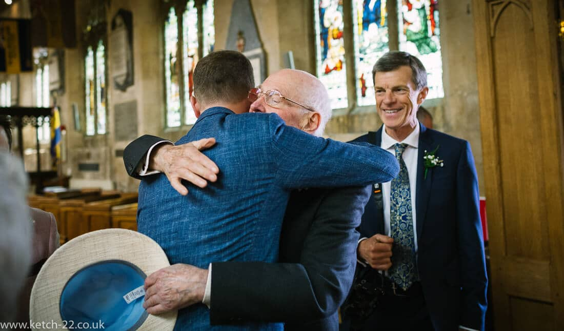 Groom hugging grand dad at church wedding