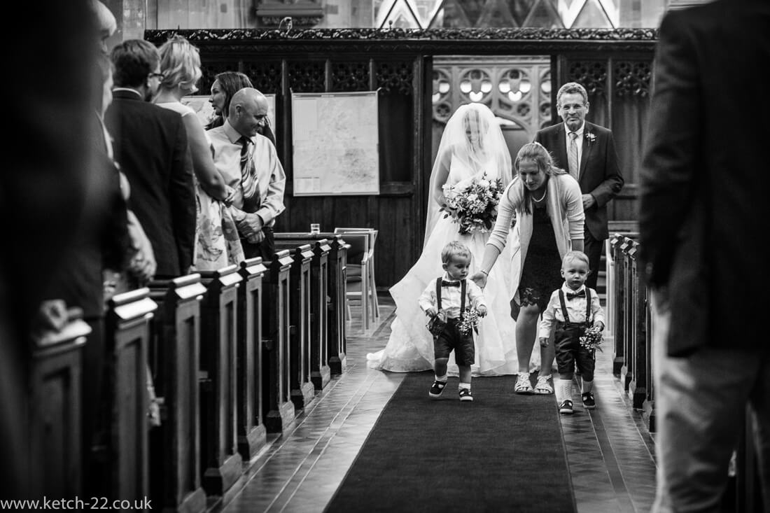 Bride, father and page boys walking down church ailse at wedding
