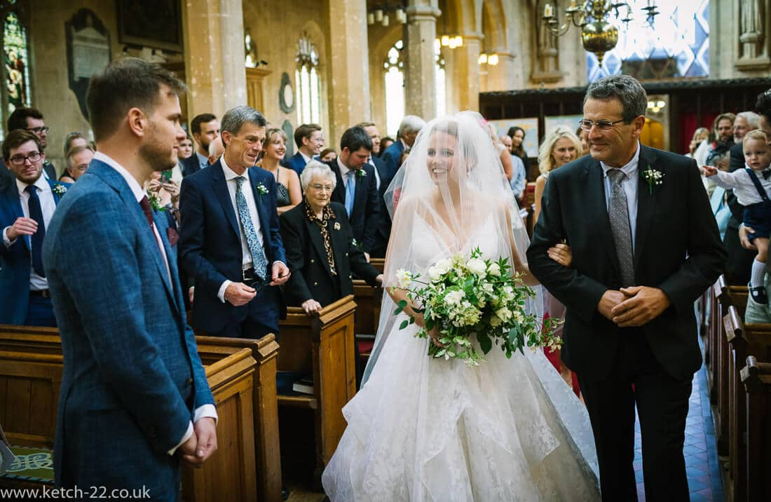 Groom takes a first look at his bride at Winchcombe church ceremony