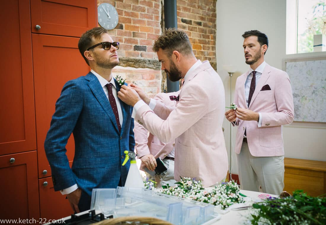 Groom with blue jacket being attended to by groomsmen with pink jackets