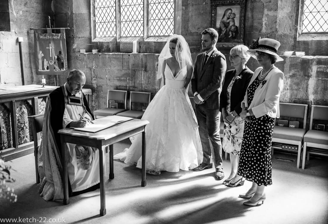 Vicar signing registrar at natural wedding