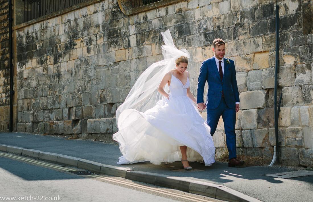 Bride and groom walking down street at summer wedding