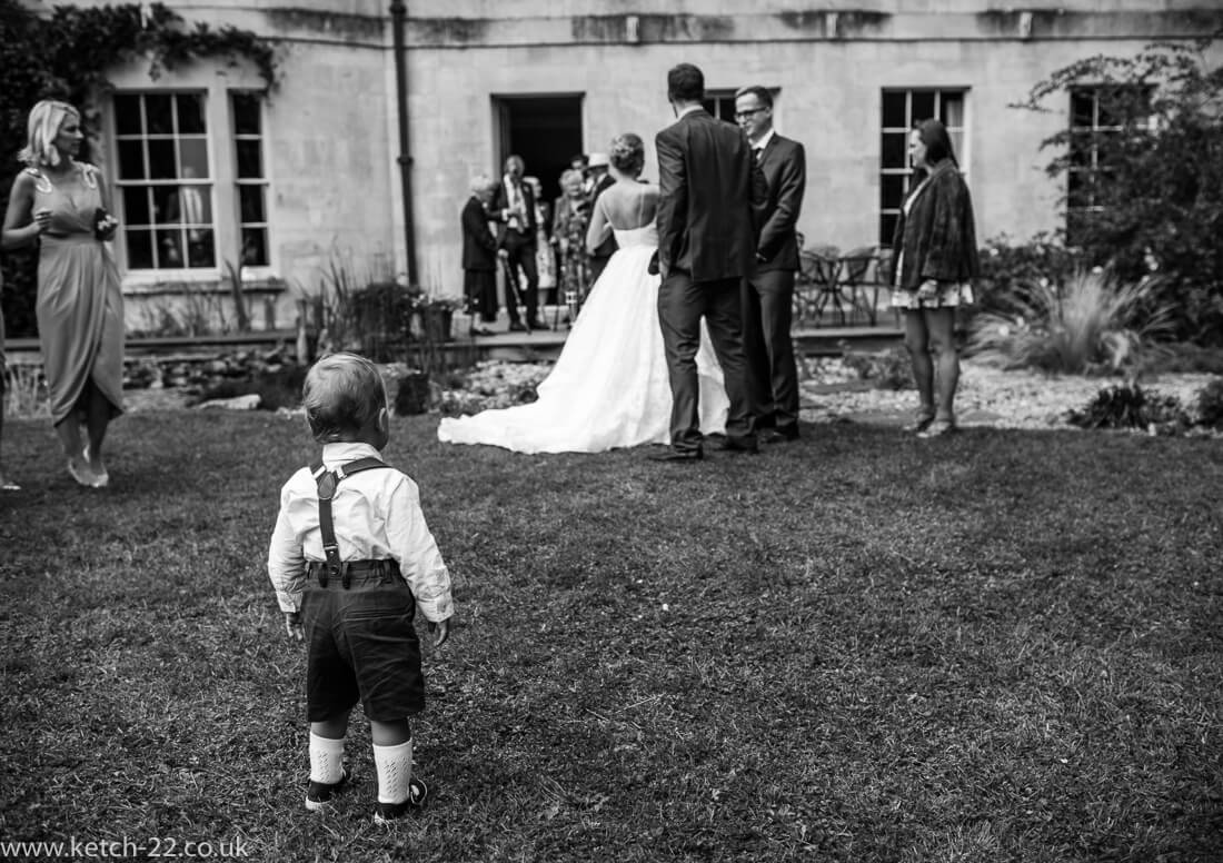 Page boy looks on as wedding guest arrive for drinks in garden