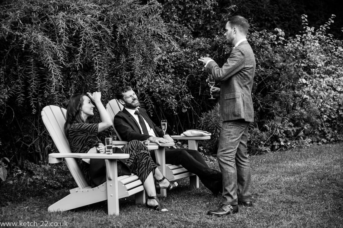 Groom chatting to seated wedding guests in garden