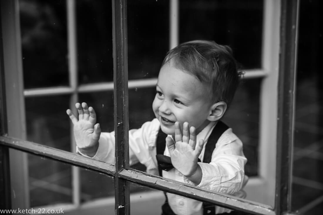 Page boy pressing his hands on window