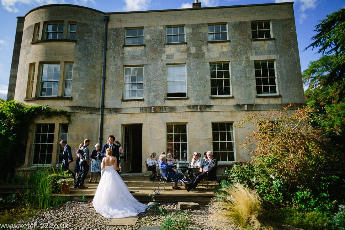 Bride and guests chatting outside country house at summer wedding