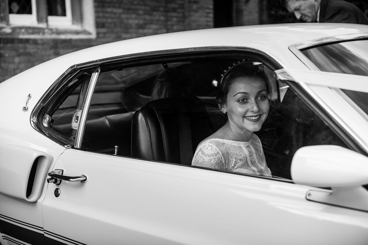 Bride looking out of GT 500 classic car at wedding