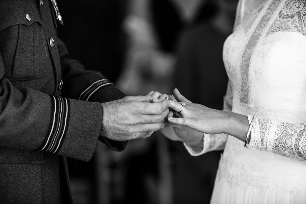 Close up of groom putting wedding rings on brides finger