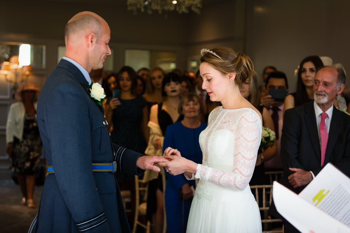 Bride putting ring on grooms finger at De Vere Latimer Estate wedding ceremony