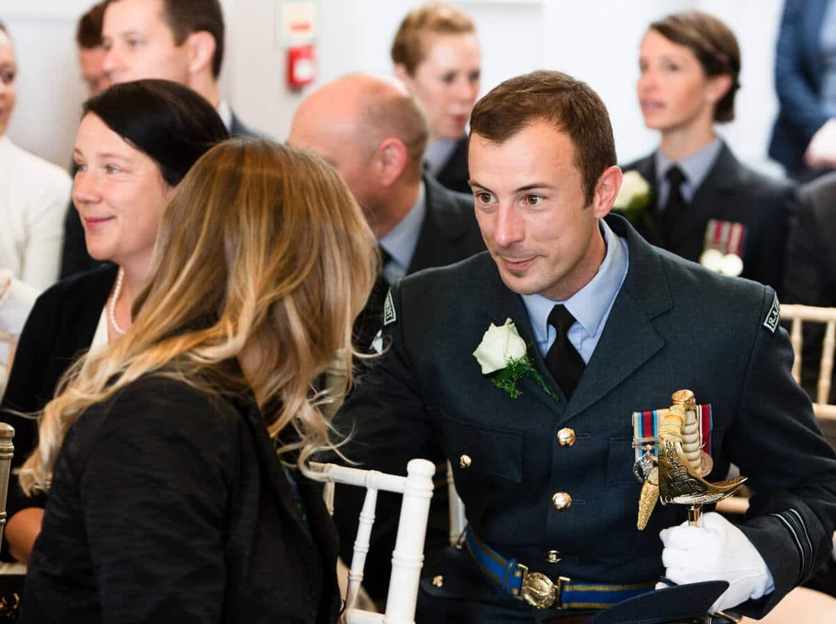 Wedding guest in RAF uniform chatting at wedding ceremony