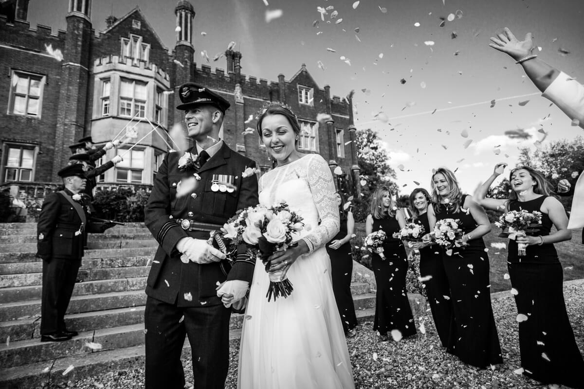 Black and white photo of bride and groom getting showered with confetti