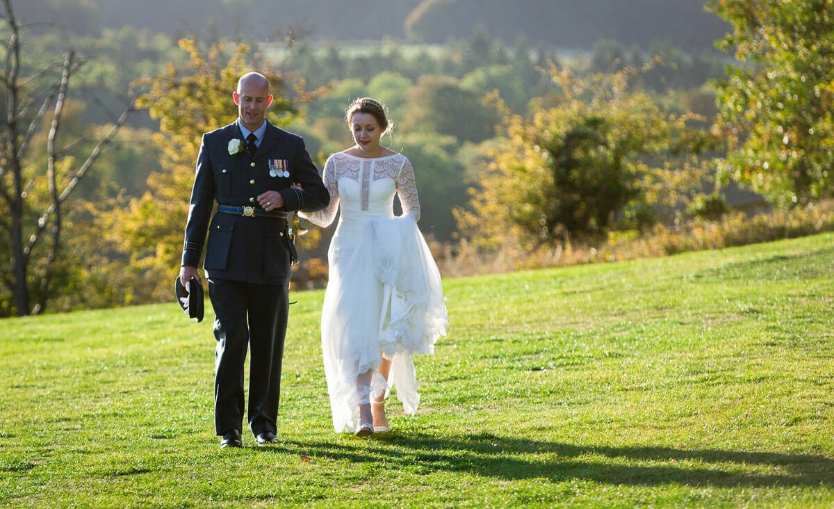 Natural wedding photo of bride and groom walking across garden