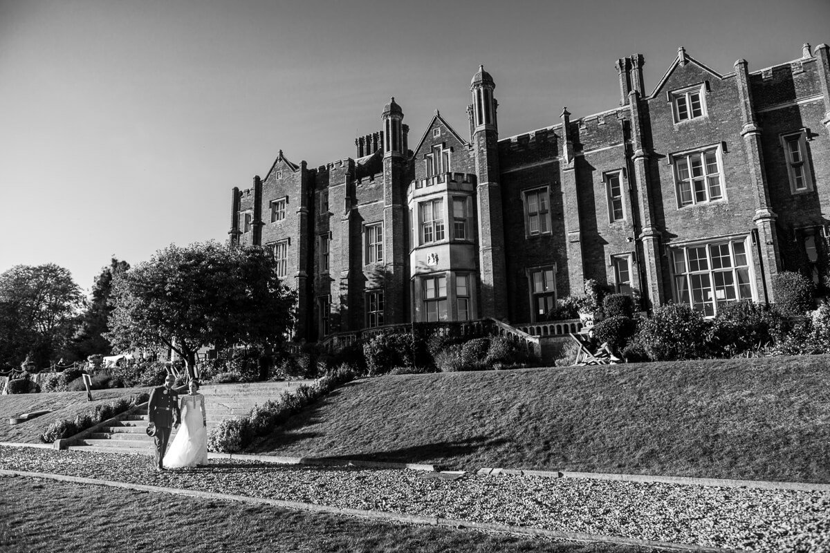 Black and white photo of bride and groom walking in front of large country house