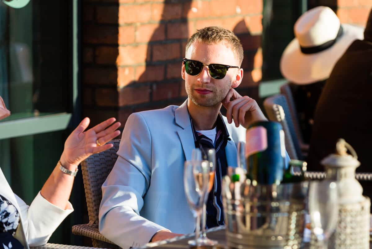 Wedding guest wearing sunglasses chatting
