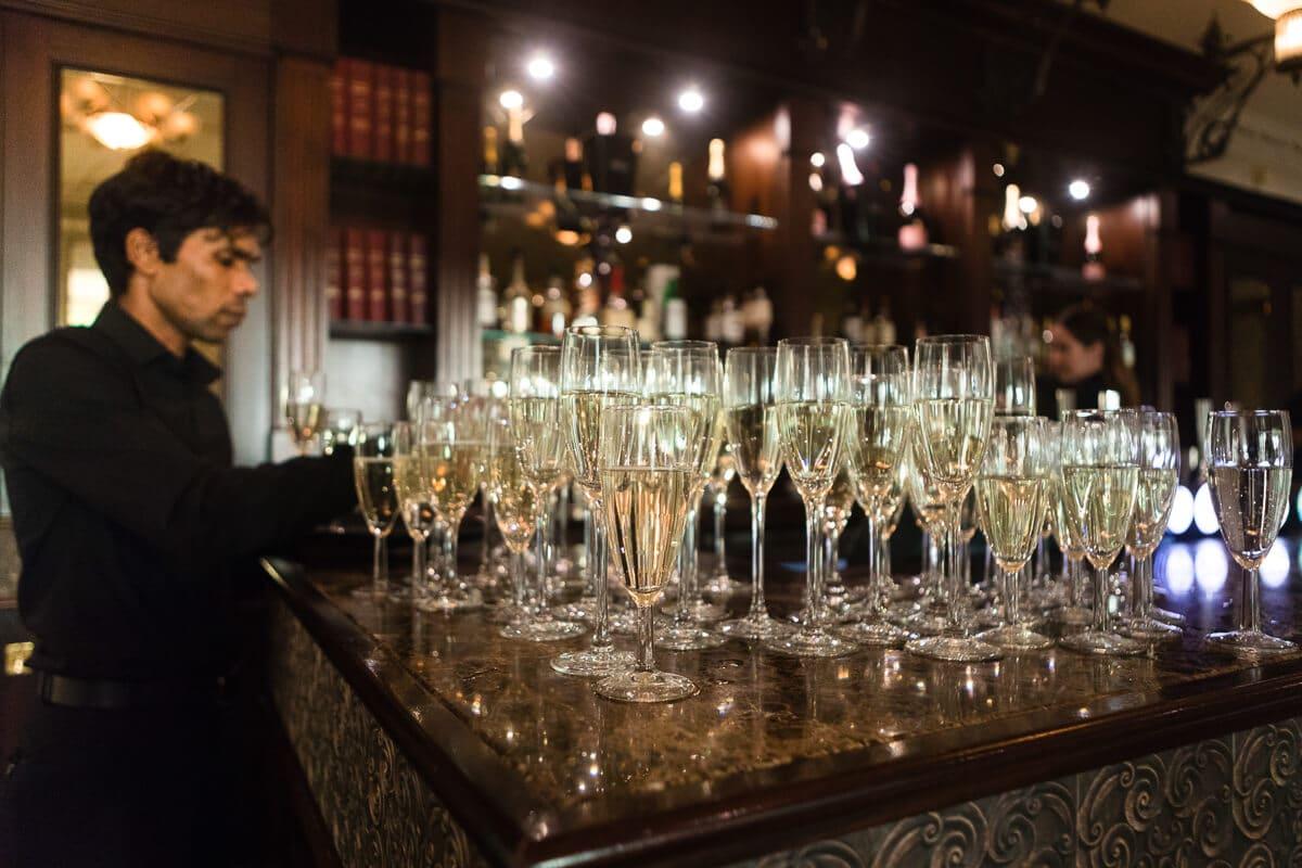Waiter arranging champagne glasses at De Vere Latimer Estate wedding