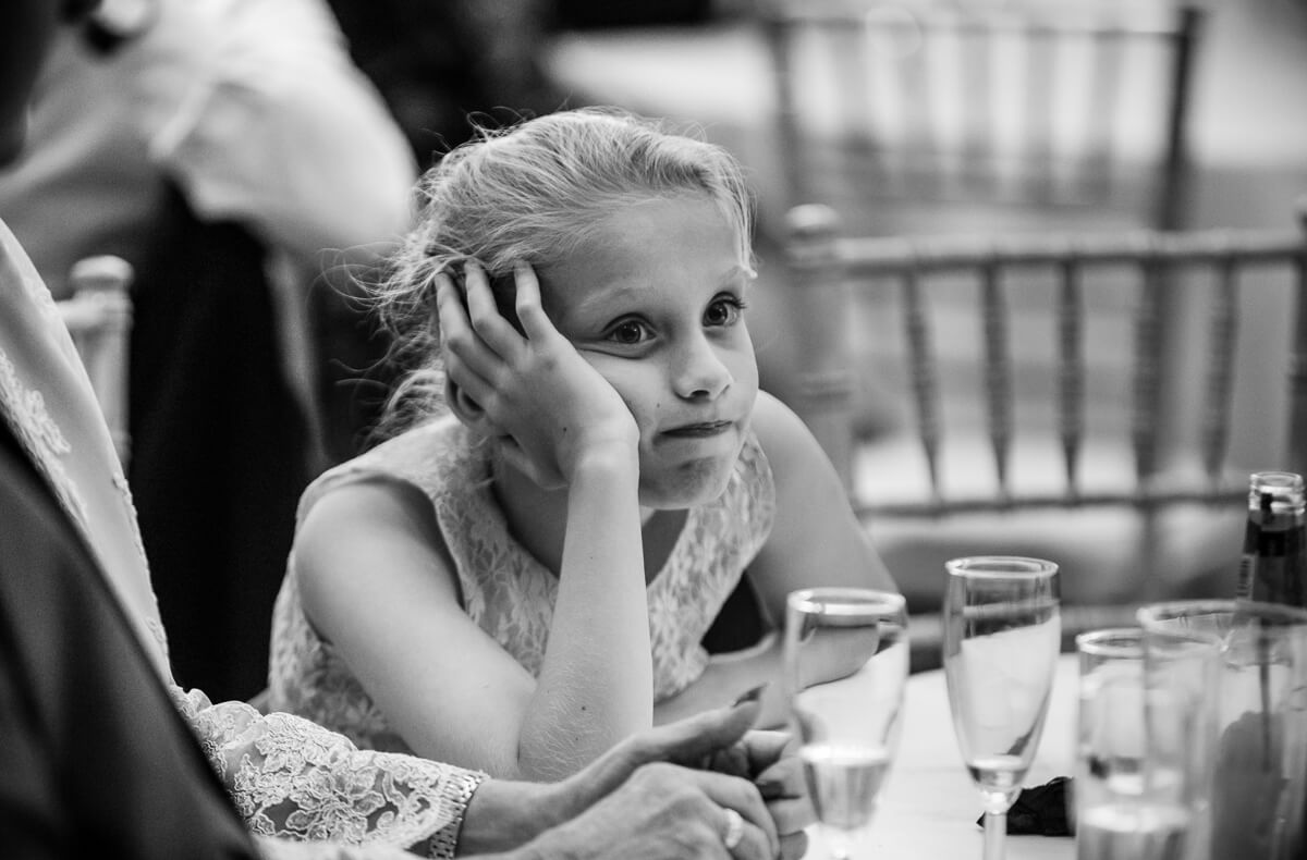Bored looking little girl at wedding speeches