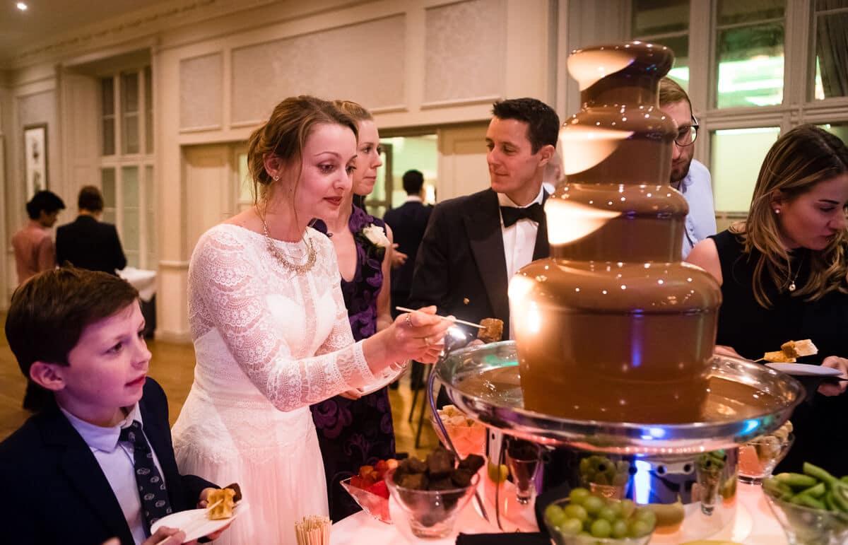 Bride enjoying chocolate fountain at wedding reception
